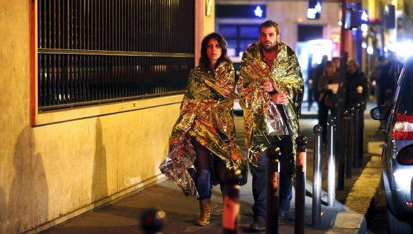 Люди согреваются под специальными одеялами недалеко от концертного зала Bataclan