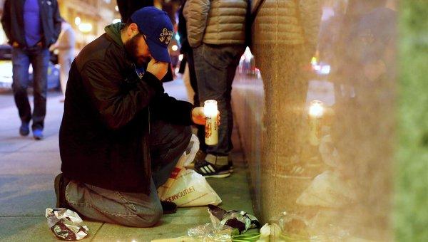 Мужчина ставит свечу возле Генерального консульства Франции