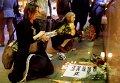 Люди возлагают цветы на импровизированный мемориал в честь жертв терактов в Париже