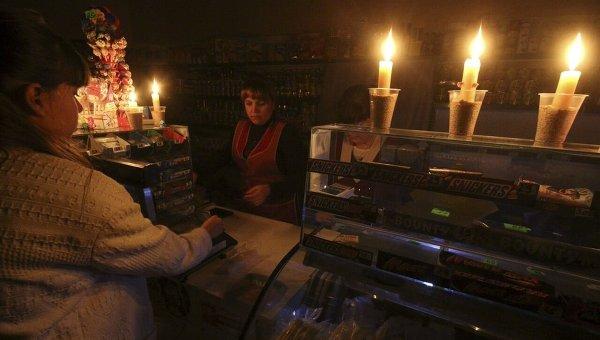 Покупатель и продавец в бакалейном магазине, работающем при свечах в Симферополе