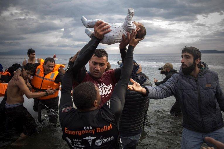 Волонтеры на Лесбосе спасают беженцев с Ближнего Востока, переправившихся из Турции.
