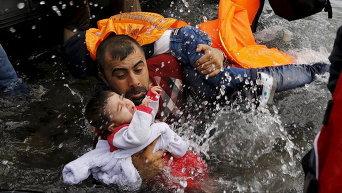 Сирийский беженец и его дети по прибытии на греческий остров Лесбос после пересечения части Эгейского моря из Турции