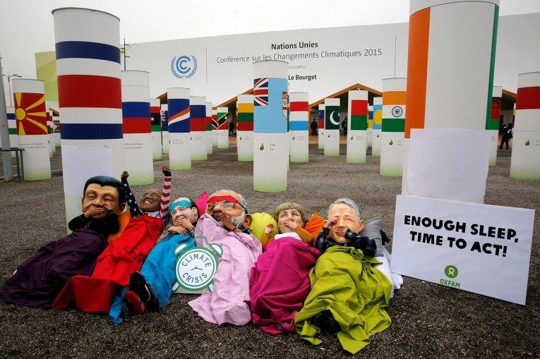 Активисты в масках лидеров государств протестуют в Париже во время проведения Климматической конференции.
