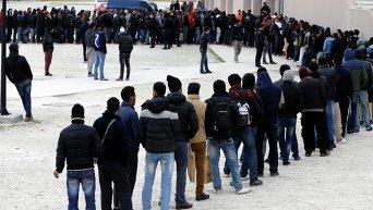 Мигранты на стадионе Фалиро в столице Греции стоят в очереди за едой