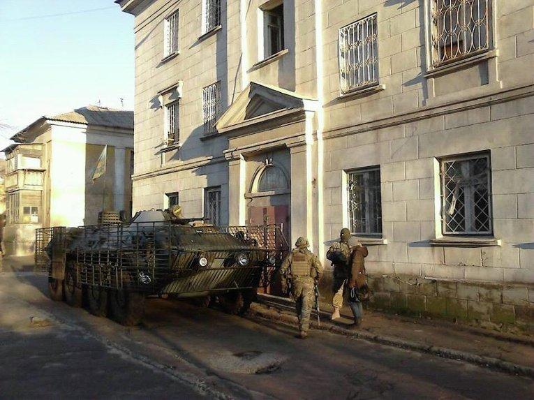 Бронетехника силовиков на месте изъятия большой партии оружия и боеприпасов в общежитии Мариуполя