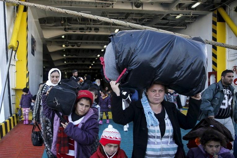 Беженцы и переселенцы прибывают на пароме с острова Лесбос в порту Пирей, вблизи Афин, Греция