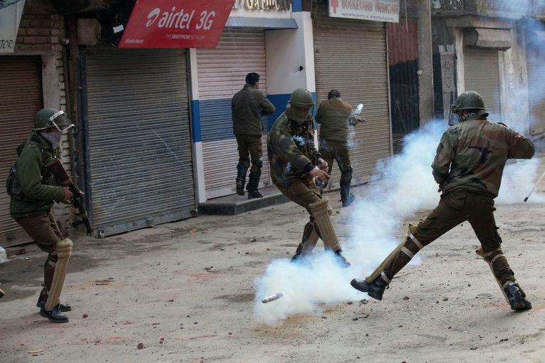 Индийские полицейские и мусульманские демонстранты в ходе акции протеста в Сринагаре, Кашмир
