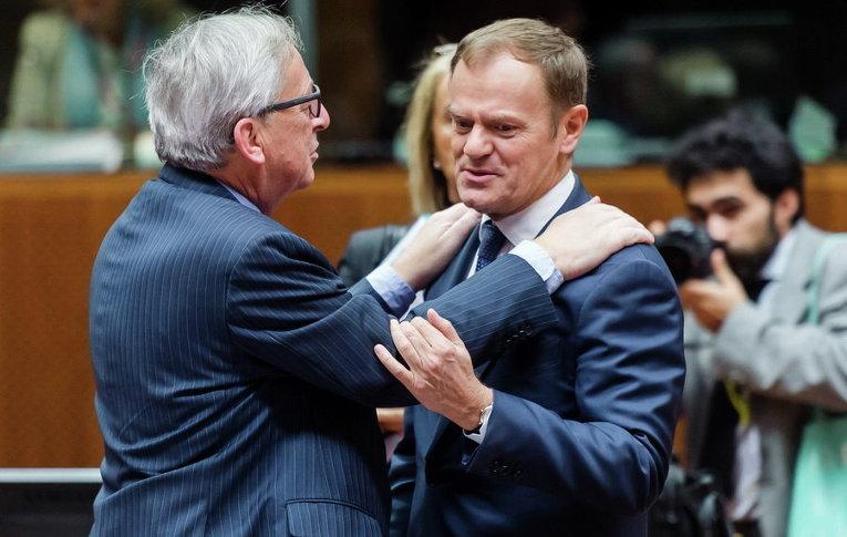 Председатель Европейской комиссии Жан-Клод Юнкер беседует с президентом Европейского совета Дональдом Туском во время заседания круглого стола саммита ЕС в Брюсселе