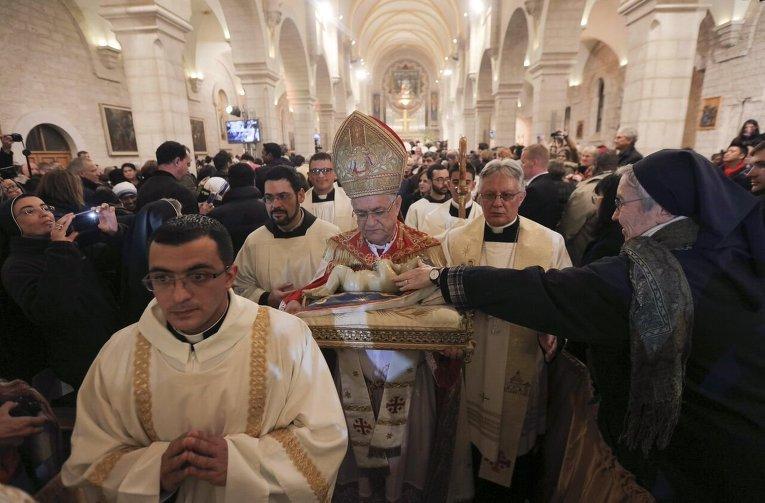 Патриарх Иерусалима латинского обряда Фуад Туаль провел всенощную мессу в церкви Рождества в Вифлееме на Западном берегу реки Иордан