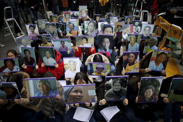 Студенты держат портреты умерших южнокорейских женщин для утех перед японским посольством в Сеуле, Южная Корея