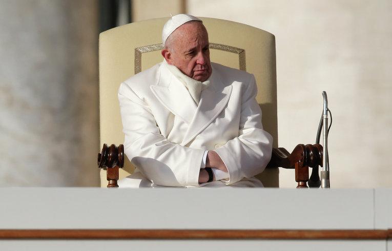 Папа Римский Франциск прячет руки от холода во время еженедельной мессы на площади Святого Петра в Ватикане