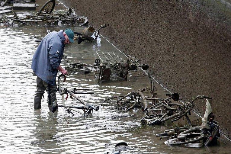 Мужчина осматривает заброшенные велосипеды во время осушения канала Сен-Мартен в Париже