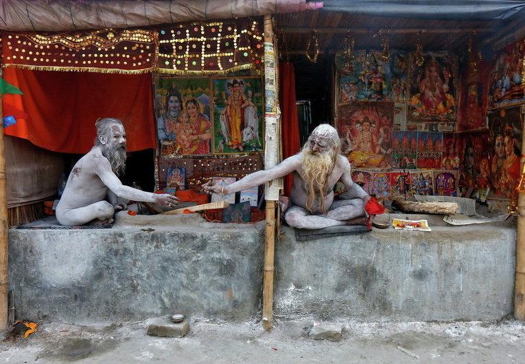 Индуистские святыы мужи, намазанные пеплом, в их временных лагерях недалеко от места слияния рек Ганг и Бенгальского залива к югу от Калькутты, Индия