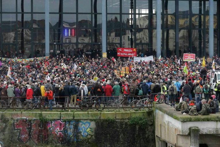 Демонстранты держат плакаты в знак протеста против изгнания фермеров с земель, на которых будет построен новый аэропорт в Нотр-Дам-де-Ланд, у суда в Нанте, Франция