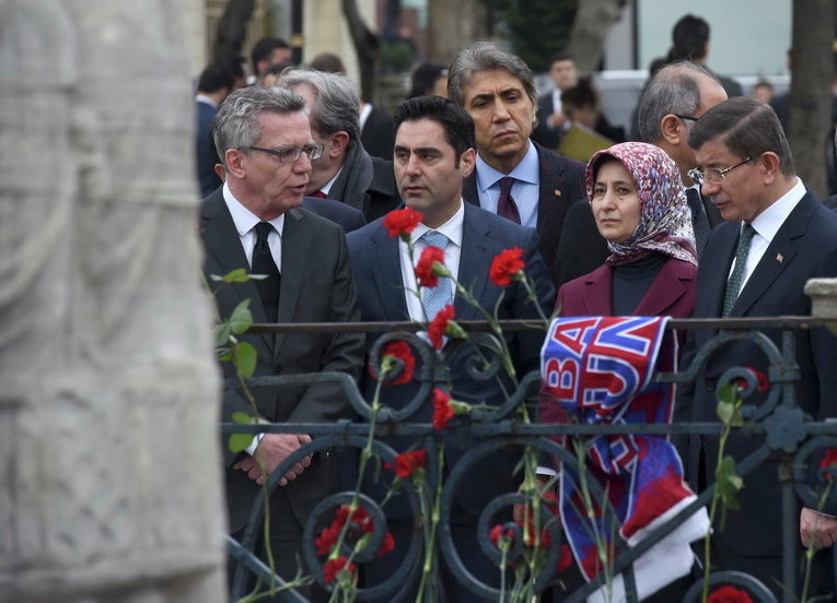 Премьер-министр Турции Ахмет Давутоглу, его жена Саре и министр внутренних дел Германии Томас де Мезьер на месте вчерашнего теракта на площади Султанахмет в Стамбуле