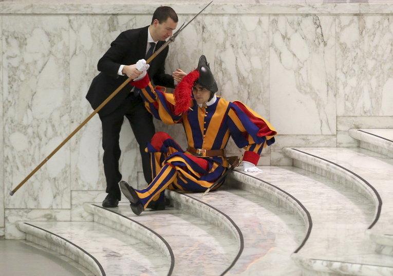 Упавшему швейцарскому гвардейцу помогают в зале Павла VI в Ватикане во время аудиенции Папы Римского
