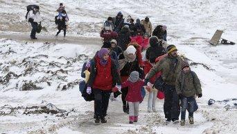 Мигранты на заснеженном поле в Сербии после пересечения македонской границы