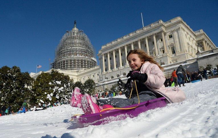 Дети катаются у Капитолия в Вашингтоне после снежной бури в столице США.