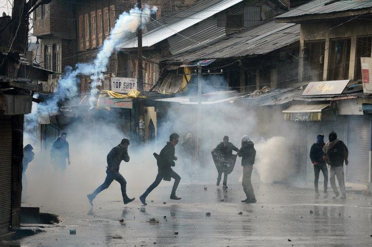 Индийские протестующие Кашмира бегут от слезоточивого газа во время столкновений в центре Шринагар