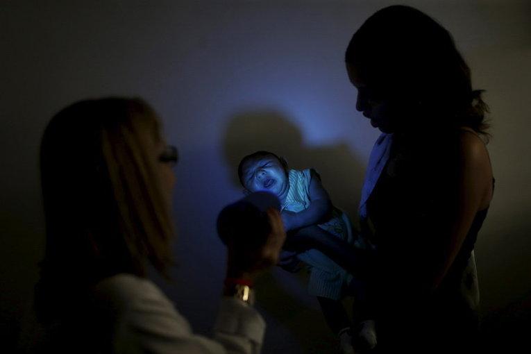 Женщина держит ребенка во время сессии стимулирования развития его зрения в реабилитационном центре Алтино Вентура в Ресифи, Бразилия