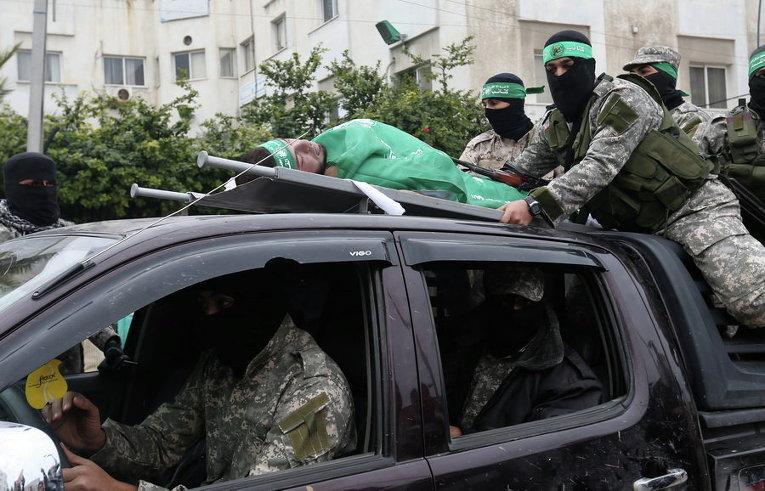 Палестинские боевики ХАМАСа везут тело одного из семи боевиков ХАМАС, который погиб при обрушении туннеля в секторе Газа