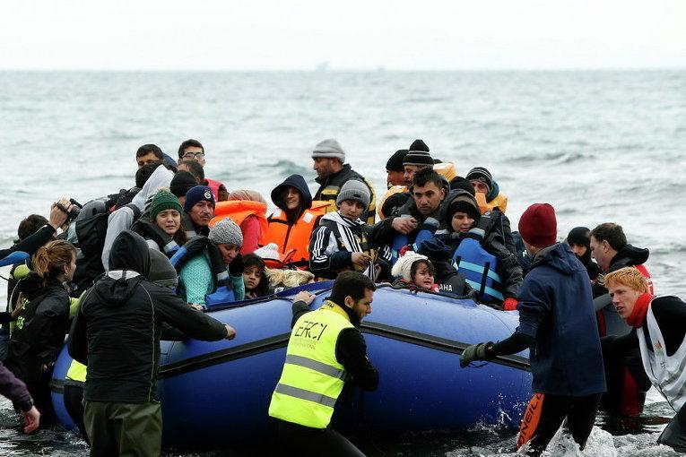 Волонтеры тянуть лодку с беженцами и мигрантами на пляже на греческом острове Лесбос