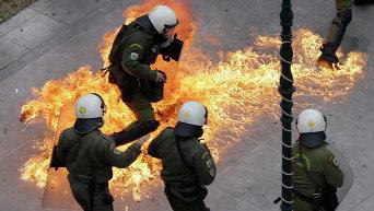 Протестующие во время 24-часовой общенациональной общей забастовки в Афинах бросают в полицейских коктейли Молотова