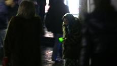 Пожилая женщина просит милостыню