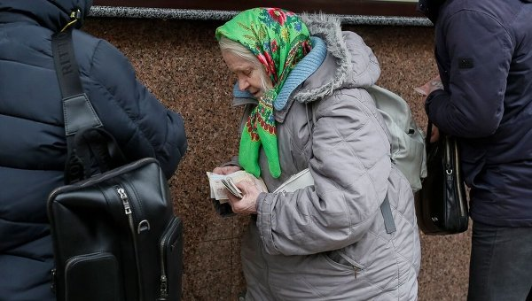 Пожилая женщина покупает продукту в центре Киева.