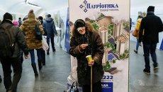 Пожилая женщина просит милостыню в метро Киева.