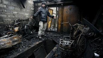 Местный житель в своем гараже, который был разрушен во время перестрелки между украинскими правительственными силами и ополченцами, на окраине Донецка