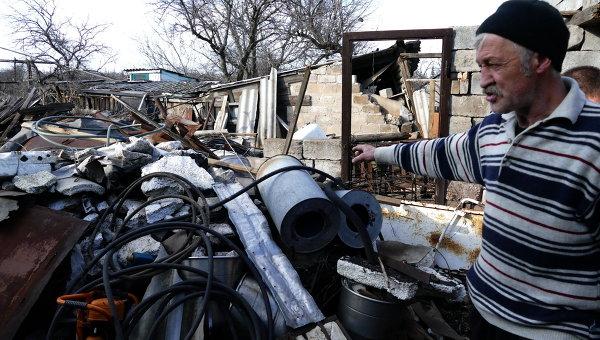 Местный житель у разрушенного дома в поселке Зайцево в Донецкой области