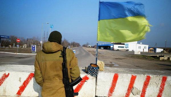 Крымский татарин активист стоит на страже у бетонных блоков на контрольно-пропускном пункте в селе Херсонской области