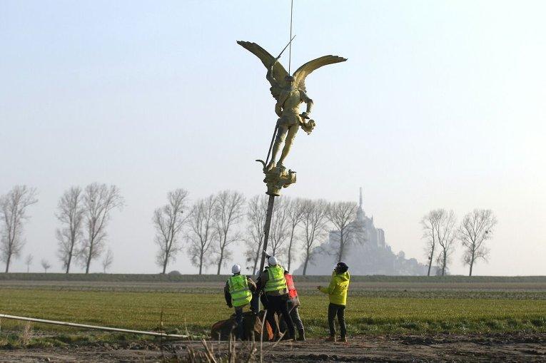 Снятие статуи Архангела Гавриила со шпиля аббатства Мон-Сен-Мишель на севере Франции для реконструкции.