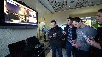 Люди стоят у телевизора в аэропорту Ростова-на-Дону, где разбился Boeing-737-800