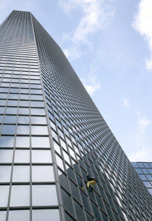 Ален Роберт, французский городской альпинист, поднимается на здание делового района La Defense, пригороде Парижа.