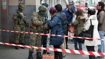 Бельгийские военные обыскивают людей, входящих на станцию метро, после нападений в Брюсселе, Бельгия
