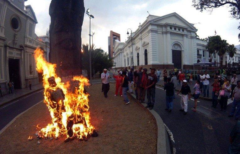 Сторонники президента Венесуэлы Николаса Мадуро сжечь куклы, изображающие президента Национального собрания Энри Лисандро Рамос Аллупа, президента США Барака Обамы и президента венесуэльского пищевого гиганта Empresas Polar, Лоренцо Мендоза