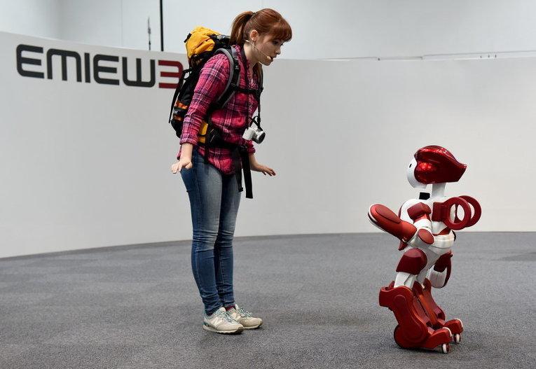 Робот EMIEW3 и представитель СМИ на выставке в Токио