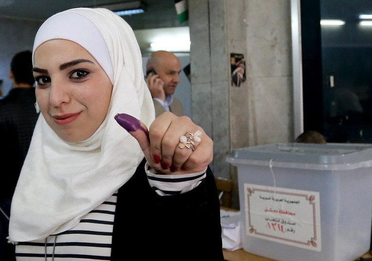 Сирийка показывает окрашенный чернилами большой палец после голосования на избирательном участке во время парламентских выборов в Дамаске