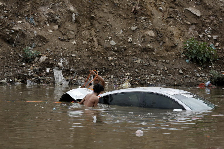 Люди пытаются вытащить автомобиль после паводков в столице Йемена Сане