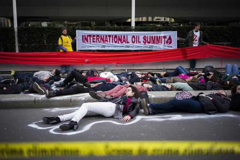 Активисты лежат на земле во время протеста против Международного нефтяного саммита в Париже