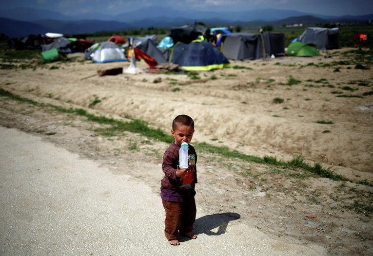 Мальчик пьет молоко в импровизированном лагере для мигрантов и беженцев на греко-македонской границы близ села Идомени, Греция