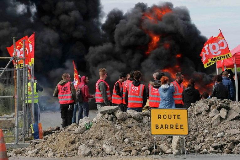 Сотрудники профсоюза нефтяного гиганта Total стоят возле горящих баррикад, чтобы заблокировать вход в депо компании вблизи нефтеперерабатывающего завода Donges, Франция