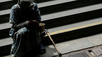Женщина, просящая милостыню на ступеньках подземного перехода
