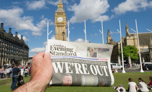 Мужчина держит в руке газету у здания парламента в Лондоне после референдума по сохранению членства Великобритании в Европейском Союзе.