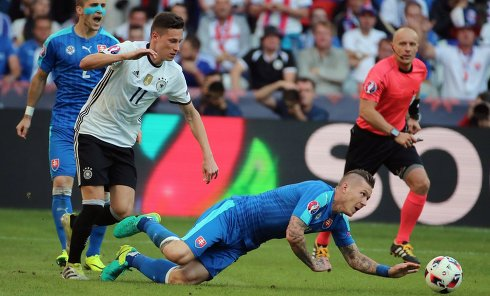 Игрок сборной Германии Юлиан Дракслер (слева) и игрок сборной Словакии Юрай Куцка в матче 1/8 финала чемпионата Европы по футболу - 2016 между сборными командами Германии и Словакии