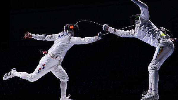 Слева направо: Юнг Сеунг-хва (Корея) и Богдан Никишин (Украина) в финальном поединке на соревнованиях командного первенства среди мужчин по фехтованию на шпагах на чемпионате мира в Москве.