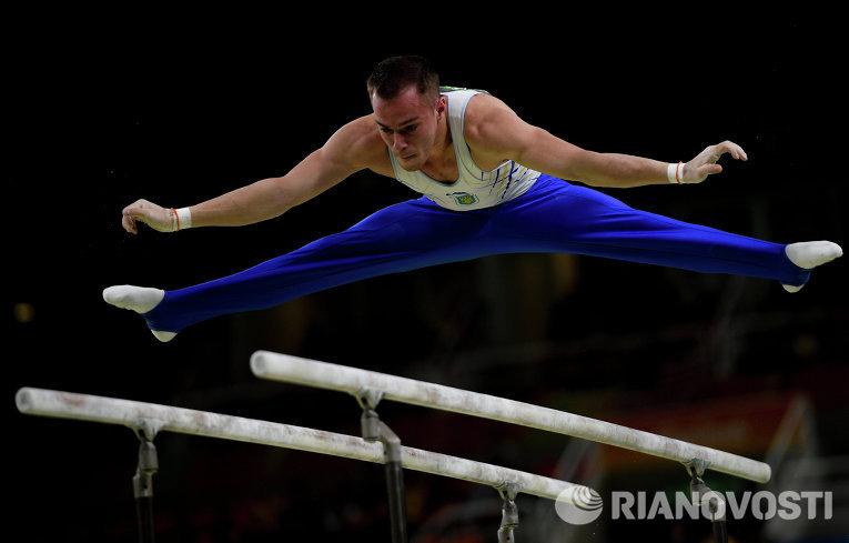 Олег Верняев выполняет упражнения на брусьях на соревнованиях по спортивной гимнастике среди мужчин