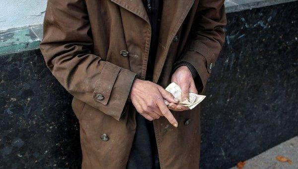 Пожилой человек считает деньги в центре Киева